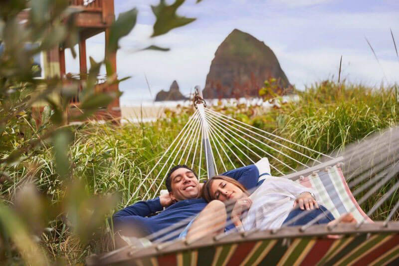 couple relaxing at surfsand resort by hotels in cannon beach