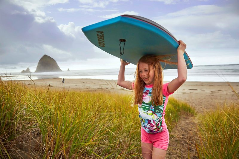 Little girl playing with a boogie board.