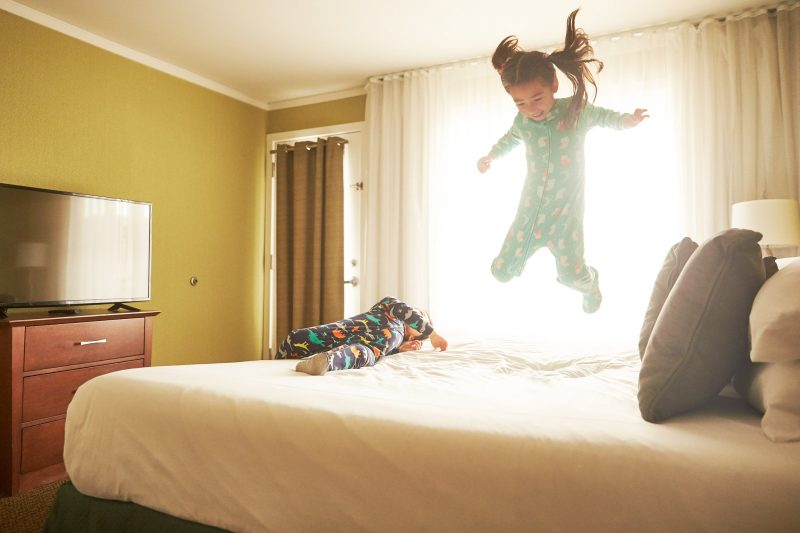 Little girl jumping on a bed.